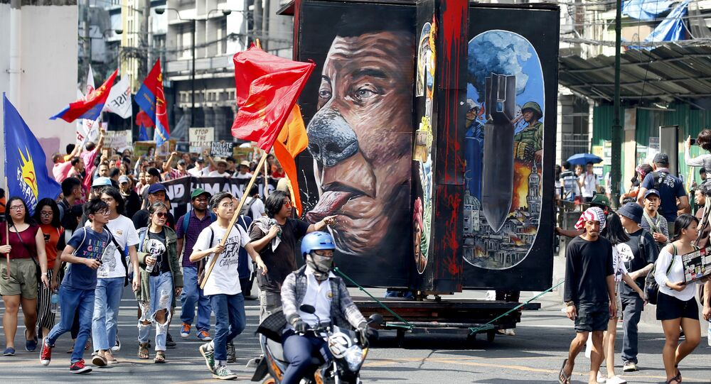 Protesters march with a rotating effigy of Philippine President Rodrigo Duterte for a rally near the Presidential Palace to mark the UN Declaration of International Human Rights Day Monday, Dec. 10, 2018 in Manila, Philippines. The protesters accuse the President of alleged rampant human rights violations since taking office more than two years ago
