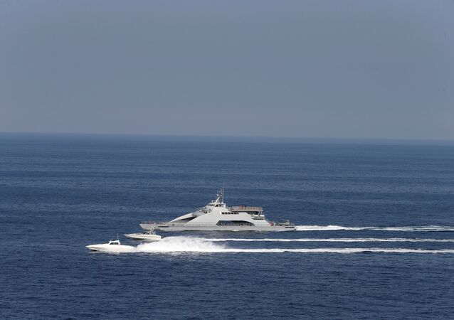 Iranian Revolutionary Guards speed boats are seen near the USS John C. Stennis carrier