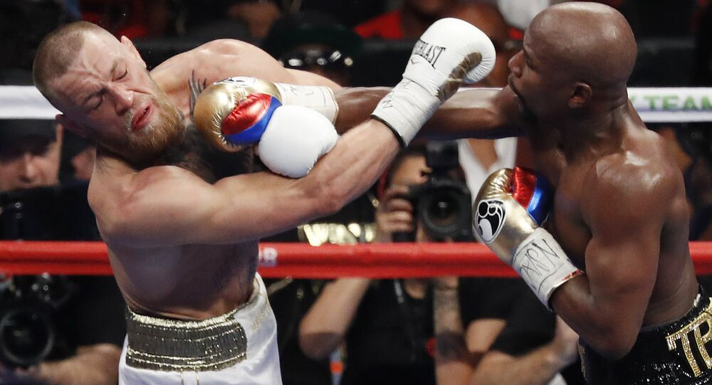 In this Aug. 26, 2017, file photo, Floyd Mayweather Jr., right, hits Conor McGregor during a super welterweight boxing match in Las Vegas