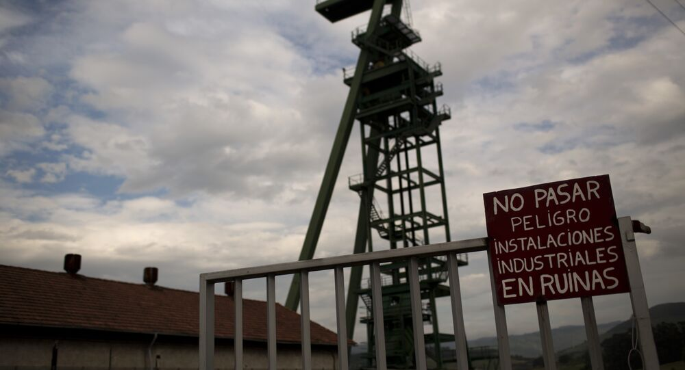 a banner reading in Spanish No entry, dangerous, industrial facilities are on the point of collapse is seen at the main entrance of La Camocha mine, abandoned five years ago because of the coal crisis in Hueces, near Gijon, Spain.