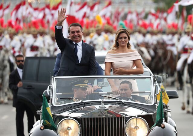 Brazil's new President Jair Bolsonaro waves as he drives past before his swear-in ceremony