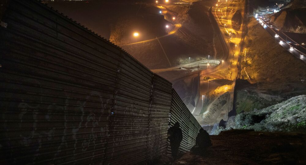 Migrants look for a place to jump the border fence to get into the U.S. side to San Diego, Calif., from Tijuana, Mexico, Saturday, Dec. 29, 2018
