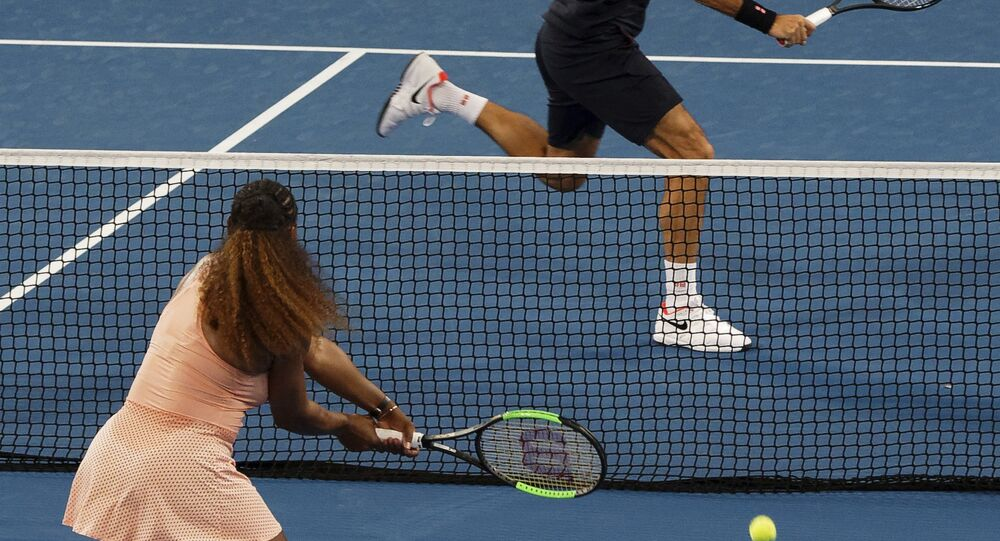 Roger Federer of Switzerland returns the ball to Serena Williams of the United states during their mixed doubles match at the Hopman Cup in Perth, Australia, Tuesday, 1, Jan. 2019