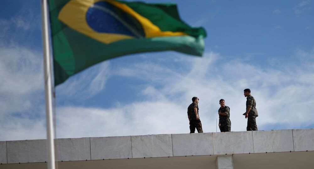 Brazilian Army soldiers are seen near the Brazilian flag