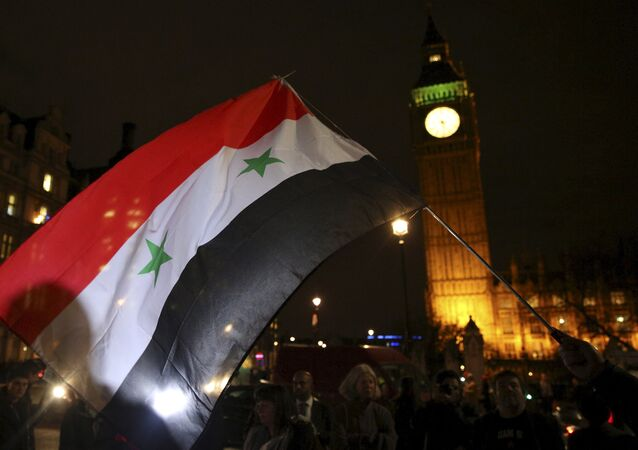 Anti-war protesters wave a Syrian flag as they demonstrate against proposals to bomb Syria outside the Houses of Parliament in London