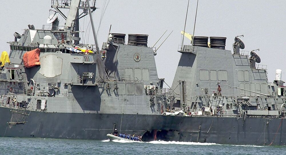 In Sunday, Oct. 15, 2000 file photo, experts in a speed boat examine the damaged hull of the USS Cole at the Yemeni port of Aden after a powerful explosion ripped a hole in the U.S Navy destroyer in the Yemeni port, killing 17 sailors and injuring some 30 others. A federal appeals court on Thursday, June 20, 2013 reinstated a lawsuit by the families of 17 sailors killed in the 2000 bombing of the USS Cole. A three-judge panel of the 4th U.S. Circuit Court of Appeals on Thursday reversed a lower court's dismissal of the lawsuit against Sudan.