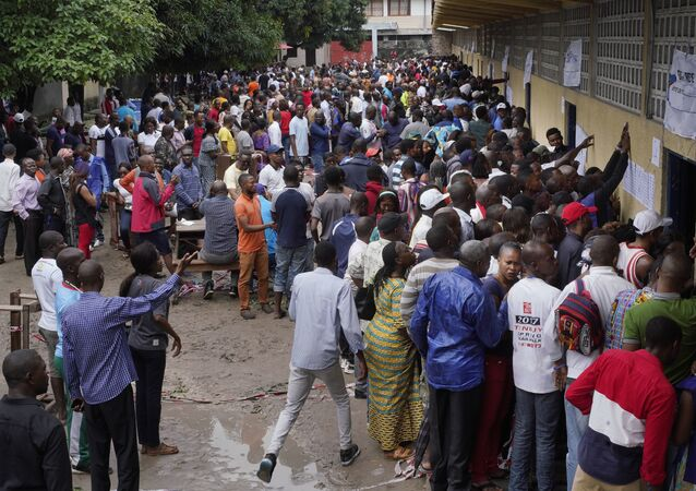 Hundreds of Congolese voters who have been waiting at the St. Raphael school in the Limete district of Kinshasa Sunday Dec. 30, 2018, storm the polling stations after the voters listings were finally posted five hours after the official start of voting. Forty million voters are registered for a presidential race plagued by years of delay and persistent rumors of lack of preparation. (AP Photo/Jerome Delay)