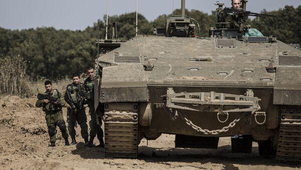 Israeli soldiers stand by a tank near the Israel Gaza border - Sputnik International