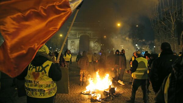 Demonstrators wearing yellow vests stands next to a burning bicycle at the Champs Elysees avenue during a protest in Paris, Saturday, Jan. 5, 2019. - Sputnik International