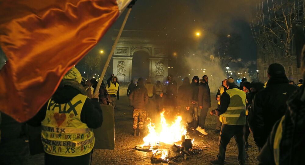 Demonstrators wearing yellow vests stands next to a burning bicycle at the Champs Elysees avenue during a protest in Paris. File photo