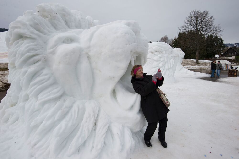 A Woman Takes a selfie in the Mouth of a Lion Snow Sculpture in Germany