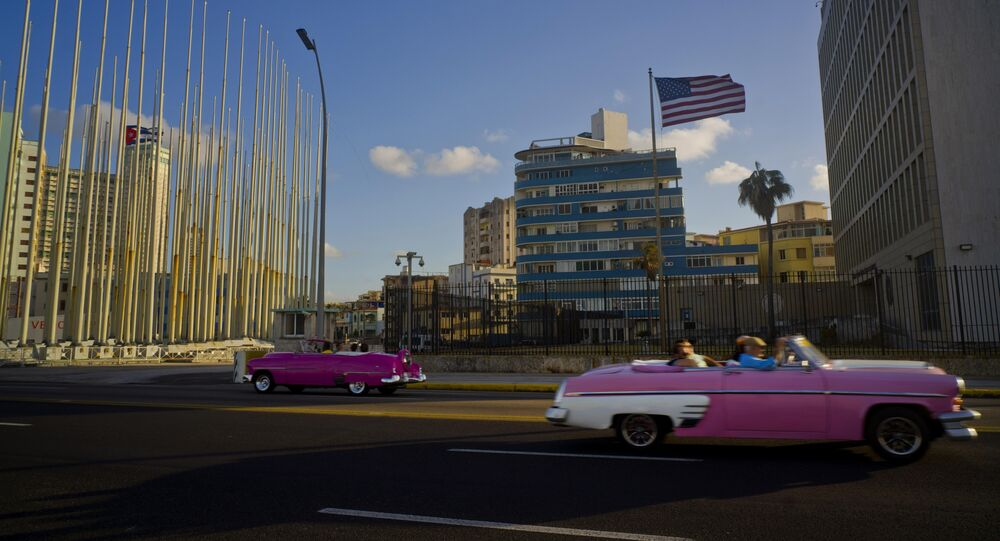 Jan. 12, 2017 file photo, tourists ride in classic American convertible cars past the United States embassy, right, in Havana, Cuba