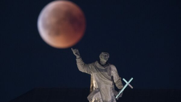 The full moon appears behind the Mattielli-statue on the Hofkirche church during a blood moon eclipse over Dresden, eastern Germany, on July 27, 2018 - Sputnik International