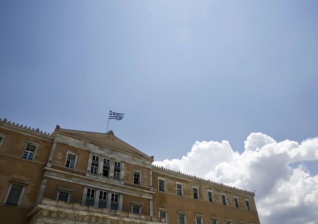 A Greek national flag flutters atop the parliament building in Athens, Greece June 29, 2015.