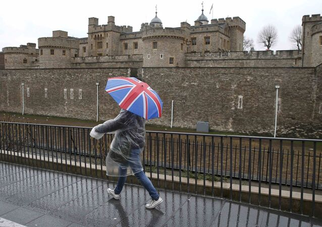 A tourist carrying a Union Flag umbrella walks in the rain during a spell of wet weather, next to The Tower of London, in London, Britain January 15, 2017.