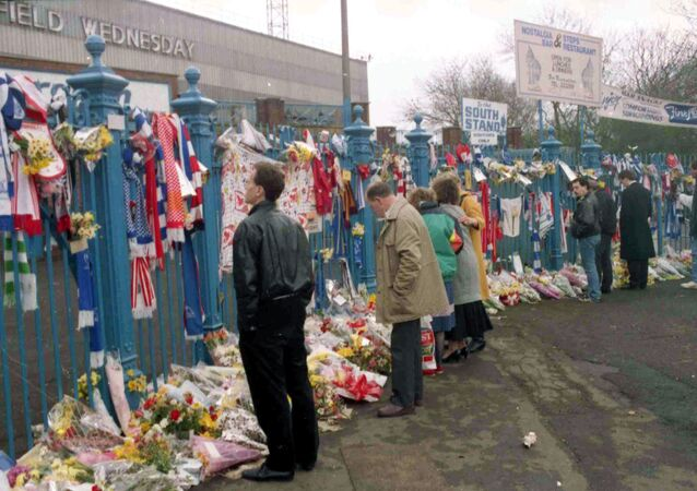 People looking at the hundreds of scarves and flowers which were left in tribute at Hillsborough in the aftermath of the disaster