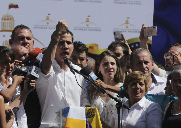 Juan Guaido, president of National Assembly, shows marks on his wrists, which he says are from handcuffs, to supporters at a rally in Caraballeda, Venezuela, Sunday, Jan. 13, 2019. The new head of Venezuela's increasingly defiant congress was pulled from his vehicle and briefly detained by police Sunday, a day after the U.S. backed him assuming the presidency as a way out of the country's deepening crisis. Guaido's wife Fabiana Rosales stands next to him, right. (AP Photo/Fernando Llano)