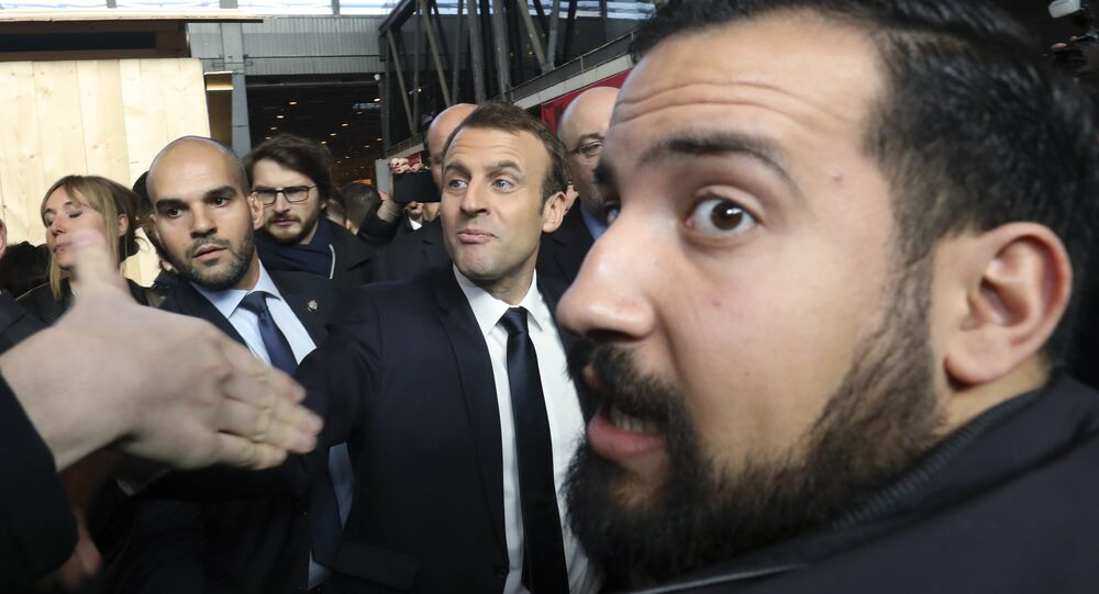 In this picture dated Feb. 24, 2017 French president Emmanuel Macron, center, visits the 55th International Agriculture Fair at the Porte de Versailles exhibition center in Paris, France, as Elysee senior security officer Alexandre Benalla, right, looks on