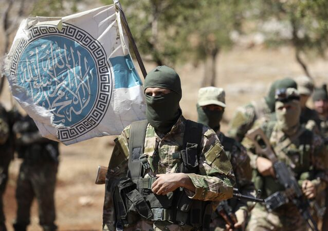 Syrian fighters attend a mock battle in anticipation of an attack by the regime on Idlib province and the surrounding countryside, during a graduation of new Hayat Tahrir al-Sham (HTS) members at a camp in the countryside of the northern Idlib province on August 14, 2018