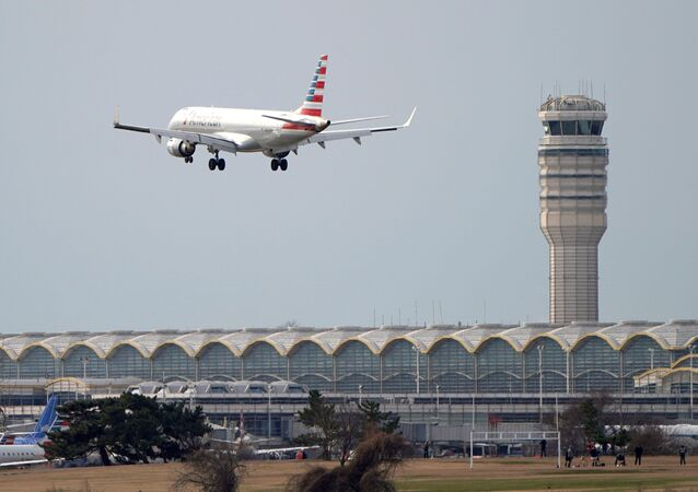 An airplane flies past the tower where air traffic controllers work despite not receiving their paychecks, on the 22nd day of a partial government shutdown at Reagan National Airport in Washington, U.S., January 12, 2019