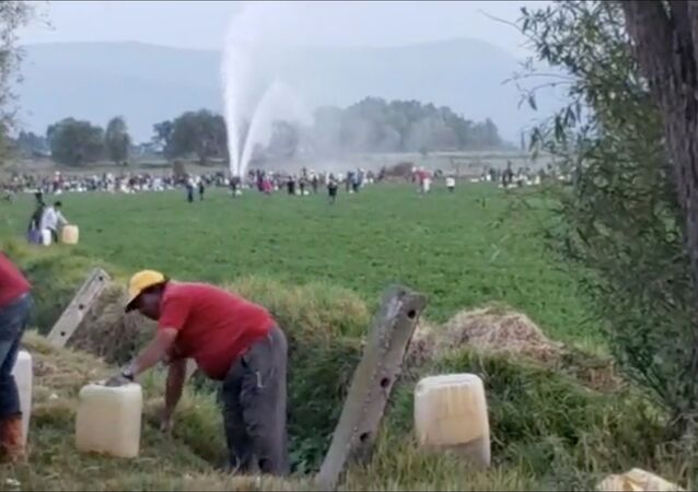 People gather at the site of a ruptured pipeline in the municipality of Tlahuelilpan, in Hidalgo