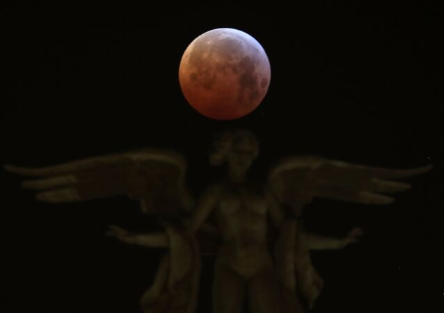 The moon is seen over Victoria Alada statue on the top of Metropoli building during a total lunar eclipse, known as the Super Blood Wolf Moon in Madrid, Spain, January 21, 2019
