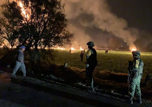 Military personnel watch as flames engulf an area after a ruptured fuel pipeline exploded, in the municipality of Tlahuelilpan, Hidalgo, Mexico, near the Tula refinery of state oil firm Petroleos Mexicanos (Pemex), January 18, 2019 in this handout photo provided by the National Defence Secretary (SEDENA)