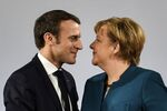 German Chancellor Angela Merkel watches French President Emmanuel Macron after the signing of a new Germany-France friendship treaty at the historic Town Hall in Aachen, Germany, Tuesday, Jan. 22, 2019