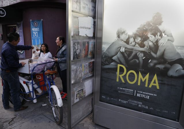 Women buy pastries from a vendor in the Roma Sur neighbourhood of Mexico City, near a poster for the Oscar-nominated film Roma