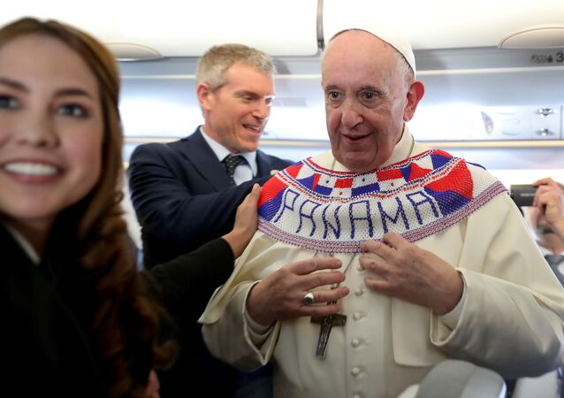 Pope Francis wears a Panama banner as he meets journalists onboard the plane taking them to Panama City, January 23, 2019