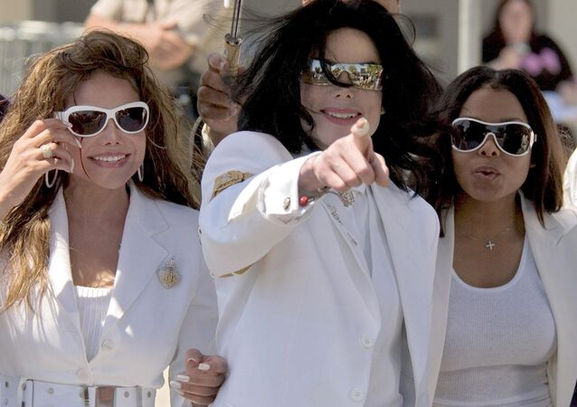 Superstar Michael Jackson (C), flanked by his sisters LaToya Jackson (L) and Janet Jackson (R) acknowledge their fans during a lunch break at a pretrial hearing at the Santa Barbara County Courthouse in Santa Maria, California, 16 August 2004.