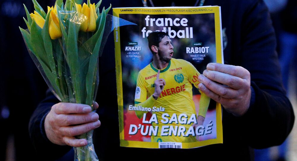 A man holds a sports magazine and yellow tulips as fans gather in Nantes' city center after news that newly-signed Cardiff City soccer player Emiliano Sala was missing after the light aircraft he was travelling in disappeared between France and England the previous evening, according to France's civil aviation authority, France, January 22, 2019.