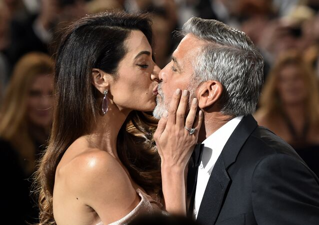 FILE - In this June 7, 2018 file photo, actor/director George Clooney gets a kiss from his wife Amal as he arrives for the 46th AFI Life Achievement Award in Los Angeles. The ceremony will air on Thursday, June 21