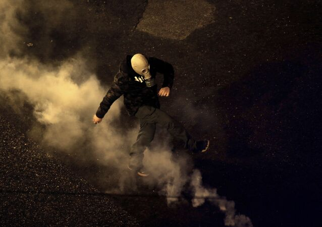 A protester kick back a tear gas canister fired by riot police during clashes following a rally by opponents of Prespa Agreement, outside the Greek Parliament in Athens, Thursday, Jan. 24, 2019