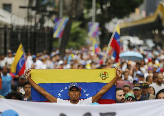 An opposition member holds a Venezuelan national flag during a protest march against President Nicolas Maduro in Caracas, Venezuela, Wednesday, Jan. 23, 2019.