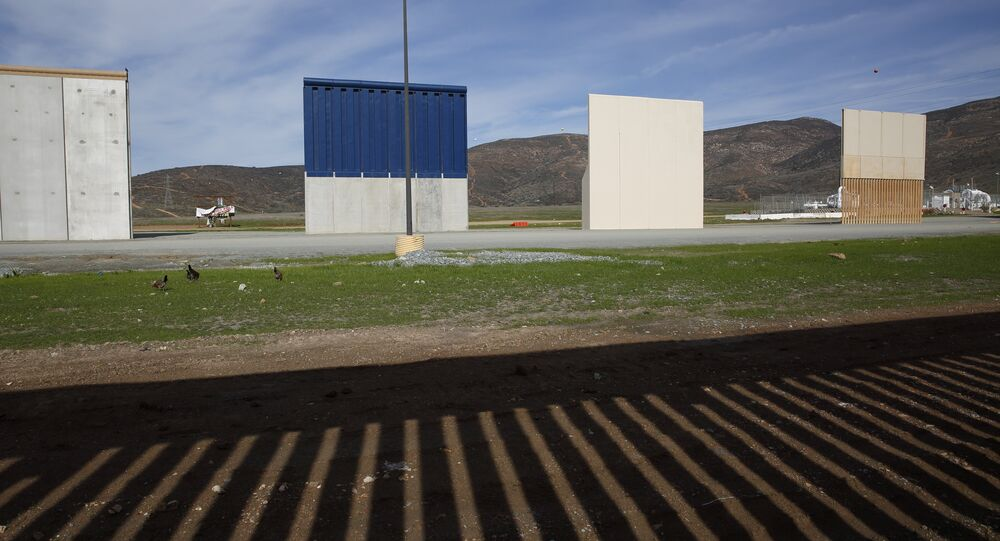 Prototypes of border wall sit behind the bars of the current border wall, Tuesday, Jan. 8, 2019, seen from Tijuana, Mexico
