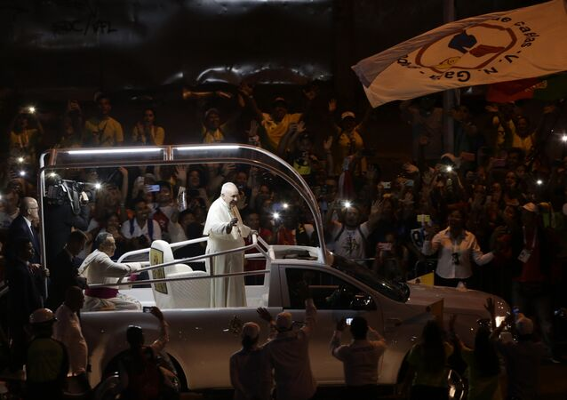 Pope Francis waves to the crowd as he rides his popemobile in Panama City