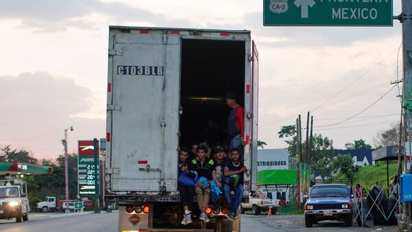 Immigrants pass by a highway sign that reads in Spanish: Mexico Border, as they take a lift in the back of a truck during their journey towards the United States, in Pajapita, Guatemala, January 17, 2019 - Sputnik International