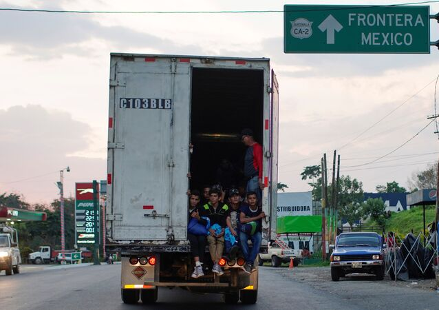 Immigrants pass by a highway sign that reads in Spanish: Mexico Border, as they take a lift in the back of a truck during their journey towards the United States, in Pajapita, Guatemala, January 17, 2019