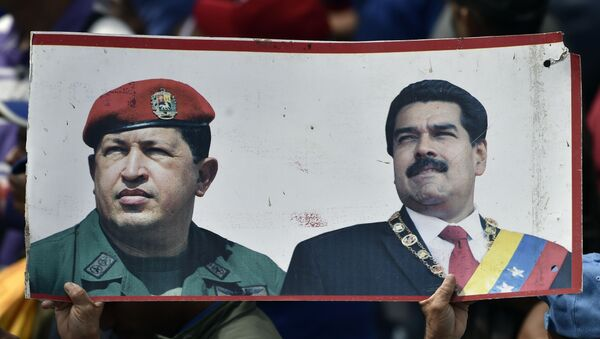 A supporter of President Nicolas Maduro's government holds a banner with the portraits of late Venezuelan president Hugo Chavez (L) and President Nicolas Maduro, while taking part in a march, on the anniversary of 1958 uprising that overthrew military dictatorship in Caracas on January 23, 2019. - Sputnik International