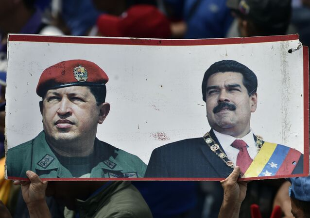 A supporter of President Nicolas Maduro's government holds a banner with the portraits of late Venezuelan president Hugo Chavez (L) and President Nicolas Maduro, while taking part in a march, on the anniversary of 1958 uprising that overthrew military dictatorship in Caracas on January 23, 2019.
