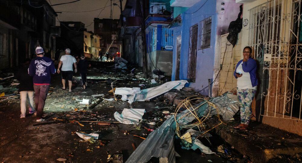 Cubans walk past debris in the tornado-hit Luyano neighbourhood in Havana early on January 28, 2019