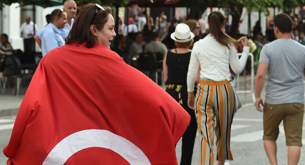 A Tunisians woman wears a national flag during a demonstration to mark Tunisia's Women's Day and to demand equal inheritance rights between men and women on August 13, 2018, in the capital Tunis