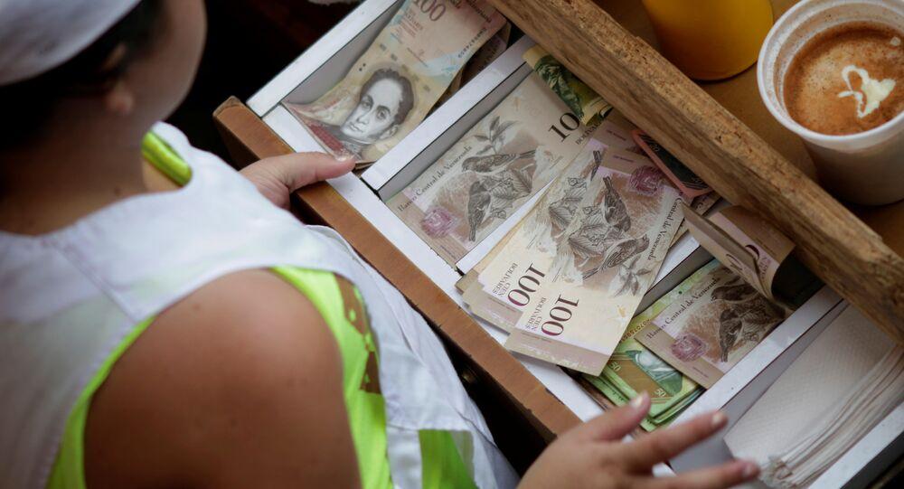 A cashier receives Venezuelan bolivar notes at a market in downtown Caracas, Venezuela
