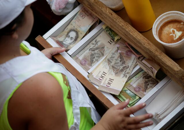 A cashier receives Venezuelan bolivar notes at a market in downtown Caracas, Venezuela