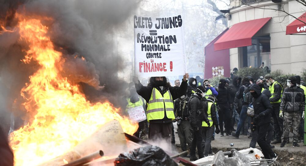 A protestor wearing a yellow vest holds a banner during the yellow vests rally in Paris, France. So-called yellow vest protests — named after the obligatory attribute of French cars — started in mid-November and have evolved into a large-scale movement against government policies and rising living costs.