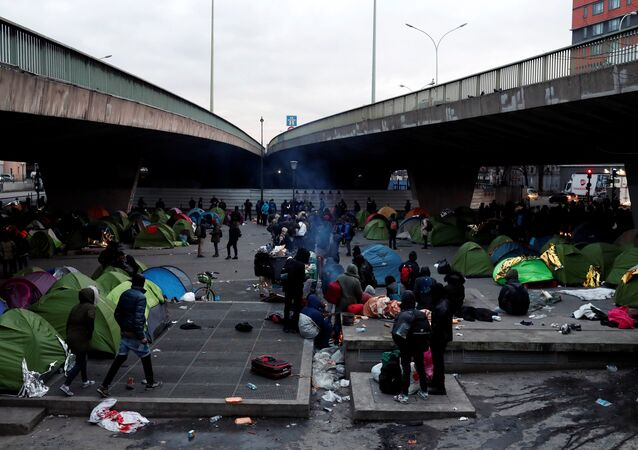 Migrants wait for the evacuation by French police of a makeshift camp set up under the Porte de la Chapelle ring bridge in Paris, France, January 29, 2019