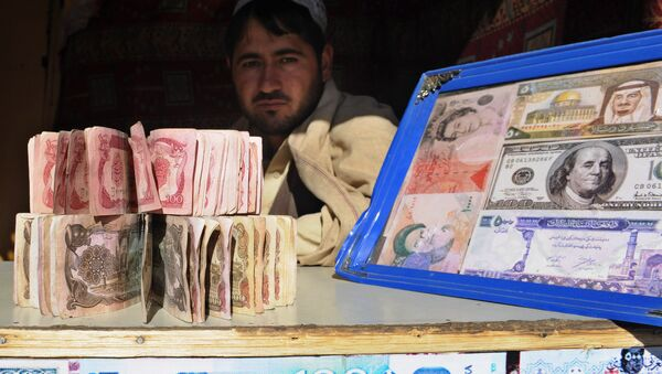 A Pakistani man holds banknotes as he waits for the customers at his currency exchange shop in Quetta on November 22, 2010 - Sputnik International