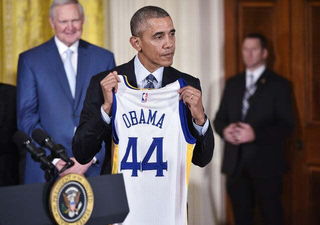 US President Barack Obama holds a jersey presented to him during an event honoring the 2015 NBA Champion Golden State Warriors in the East Room of the White House on February 4, 2015 in Washington, DC.
