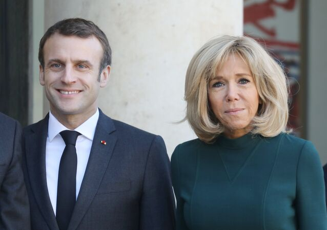 French President Emmanuel Macron (L) and his wife Brigitte Macron wait for the arrival of Quebec's Prime Minister at the Elysee Palace in Paris on January 21, 2019.